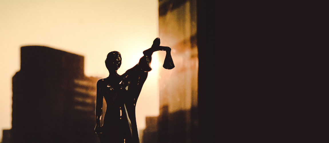 Silhouette-of-Woman-Holding-Scales-Of-Justice-with-City-Building-in-Background