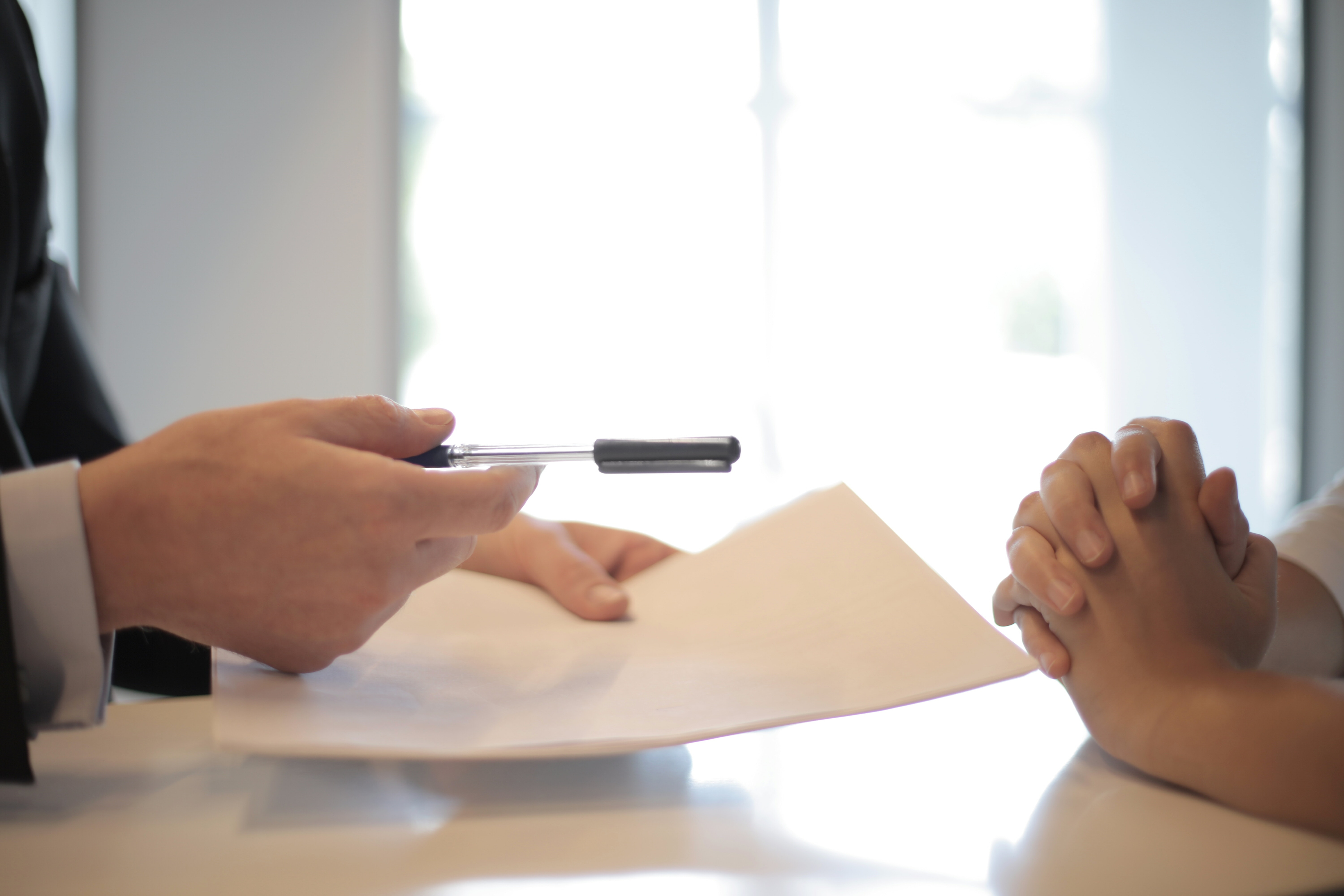 Handing-A-Pen-And-Contract-To-Person