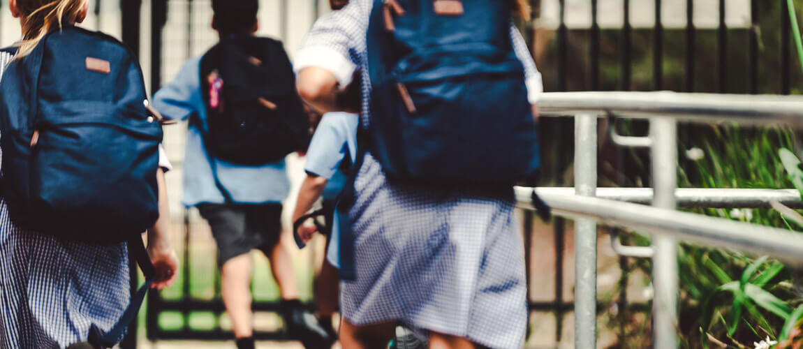School children wearing uniforms and carrying backpacks.